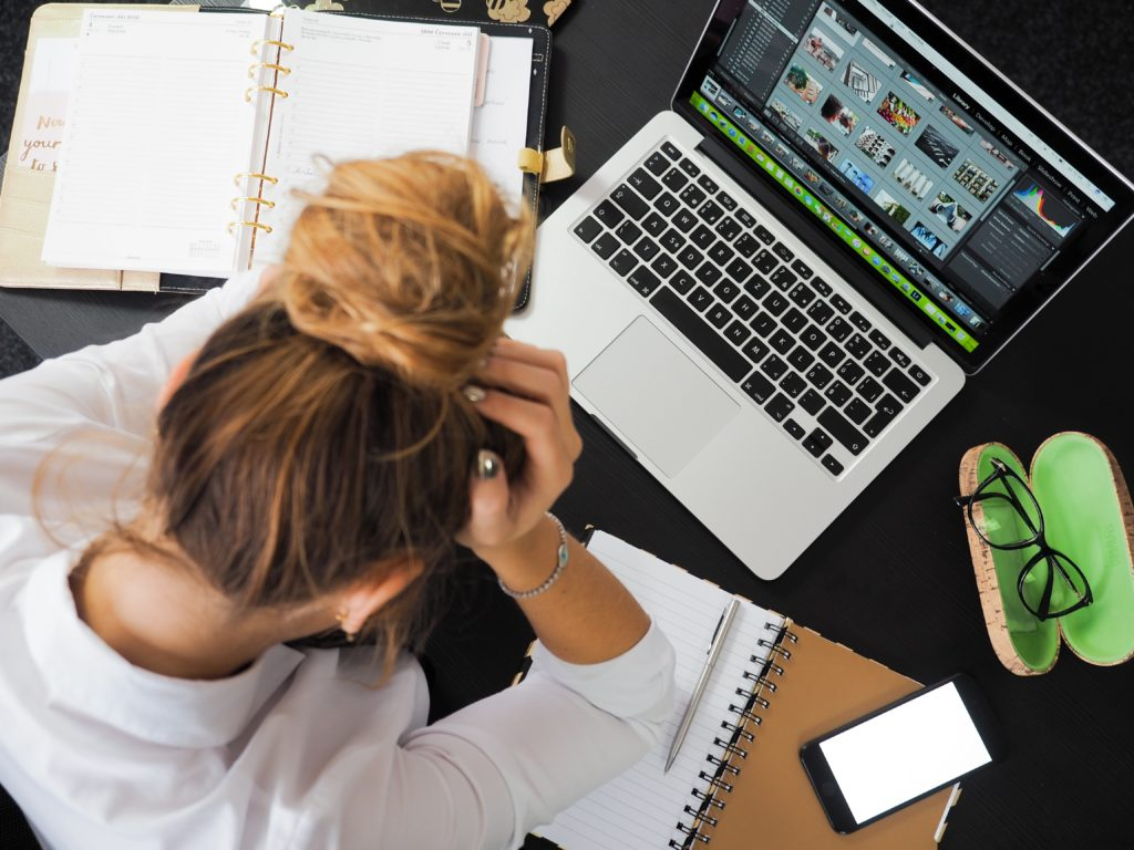 femme tenant sa tête entre ses mains devant un ordinateur